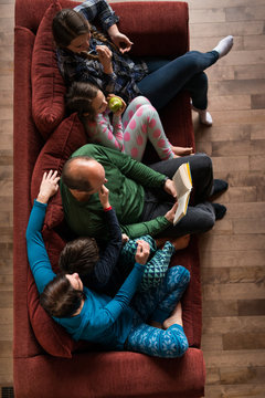 Overhead view family in ski chalet relaxes on sofa