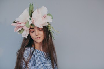 Dreamy portrait of beautiful shy girl with wreath with paper flowers