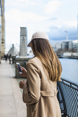 Beautiful woman using mobile phone in the city. Real lifestyle in London. UK.