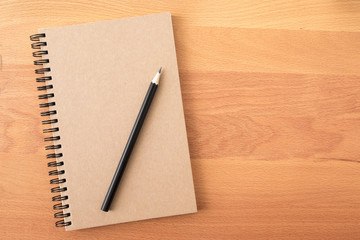 Top view of open spiral blank notebook with pencil on wood desk background