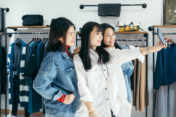 Girlfriends taking selfie in clothing store