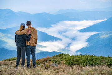 The man and a woman standing on the mountain landscape background
