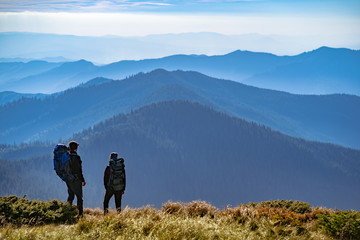 The two people standing on the mountain
