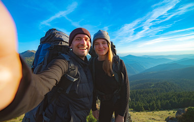 The happy couple taking a selfie on the mountain background