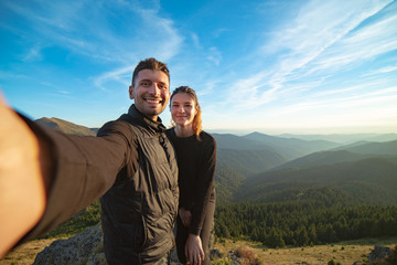 The smiling couple taking a selfie on the mountain background
