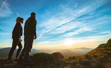The couple standing on the beautiful mountain sunset background