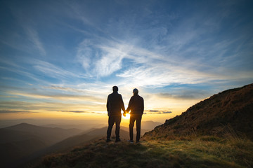 The couple standing on the rock with a picturesque sunrise