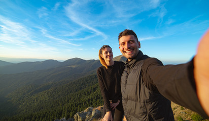 The beautiful couple taking a selfie on the mountain background
