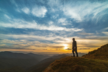 The man standing on the rock with a picturesque sunset