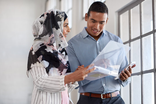 Female muslim manager talking to colleague