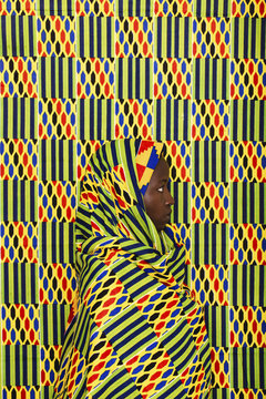 Portrait of a woman camouflaged with colorful fabrics