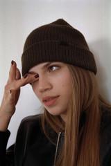 Woman in hat wiping eye