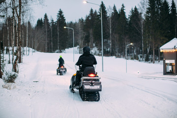 back view shot of two unrecognizable people riding snowmobiles