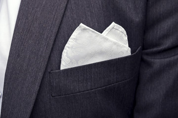 View to the male coat pocket with a fixed white square. Men's suit accessories. Wedding male guest's attire. Male wedding style. Formal dinner outfit for men. Elements of suit. Pocket square folding.