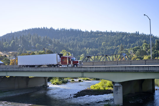 Red classic big rig semi truck with refrigerated semi trailer transporting cargo on interstate highway with bridge across the river