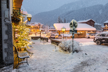 Alpine village under the snow. Macugnaga at dusk, an important winter and summer tourist resort at the foot of Monte Rosa, Main square in the center of the village during the Christmas period