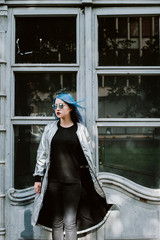 Young woman with blue hair posing against the door