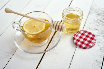delicious hot tea with lemon and honey on an old white wooden table
