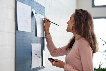 young woman working, writing on notice board