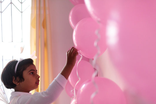Little girl on her birthday decorating with ballons and ribbons