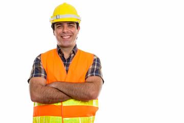 Studio shot of young happy Persian man construction worker smili
