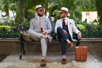 Two stylish men with suits, hats and sunglasses