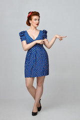 Check this out. Attractive gorgeous young European female with curvy perfect body posing in studio in stylish retro clothes, having amazed expression, pointing fore fingers at copyspace wall