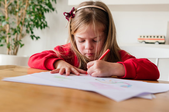 Little girl painting at home.