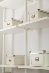 Many white closed boxes for home organizer arranged on shelf in a room
