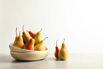 Plate with ripe pears on table against light background. Space for text