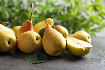 Ripe pears on grey table against blurred background