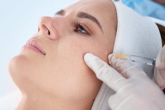 Woman undergoing face biorevitalization procedure in salon, closeup. Cosmetic treatment