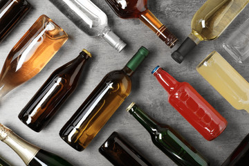 Bottles with different alcoholic drinks on grey background, flat lay