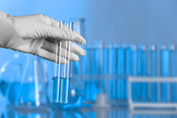 Scientist holding test tubes with liquid for analysis in laboratory. Space for text