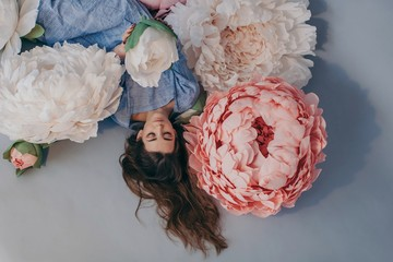 Dreamy portrait of young beautiful girl with long hair posed with big paper flowers of pastel colors