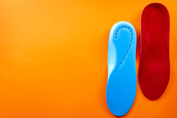 Foot support and healthy feet concept with orthopedic shoe insoles isolated on orange background with copy space