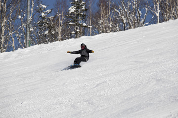 A snowboarder on slope in ski field
