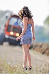 Donna con abito corto vicino al trattore durante lavoro agricolo