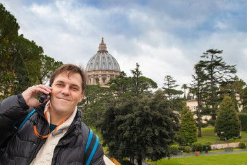 Middle aged tourist man with audio guide in his hand against the background of St. Peter's Basilica in the Vatican.
