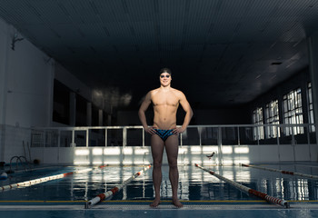 Sportive swimmer standing in sunny pool
