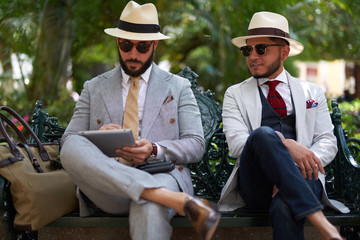 Two stylish men in a park using a tablet
