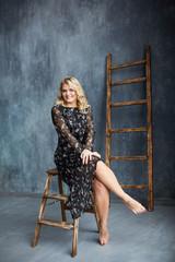 Blonde girl in dark light dress barefoot in studio