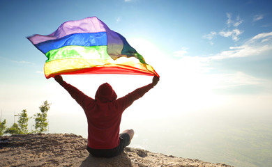 man sitting on mountain top raised rainbow LGBT symbol flag to bright sunny blue sky