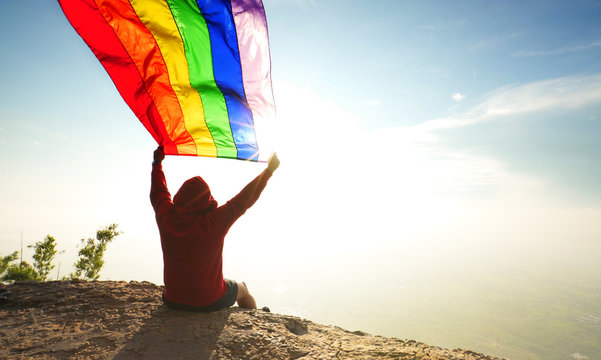 man sitting on mountain top waving rainbow LGBT symbol flag in bright sunlight blue sky