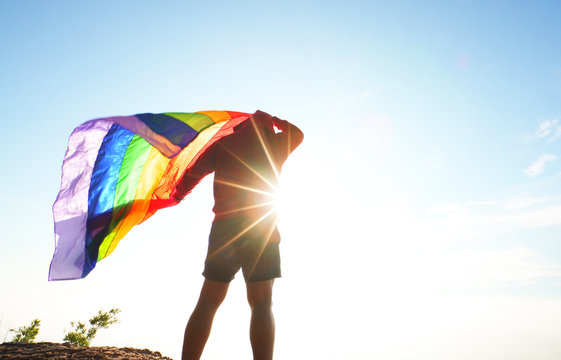 man standing on mountain top viewpoint raised rainbow LGBT flag to the sky