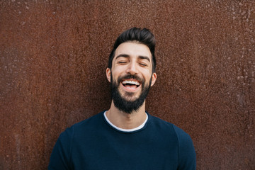 Laughing good-looking man with closed eyes.