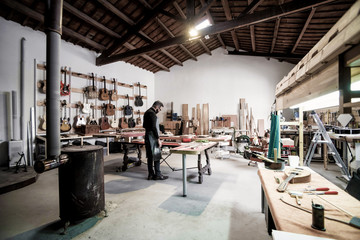 Young guitar luthier working in his workshop