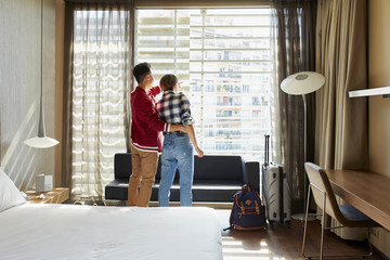 Loving Couple Looking Through Window Of Hotel Room