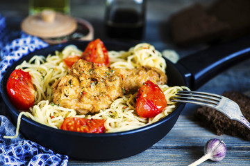 grilled chicken leg and pasta in a pan with vegetables and spices on a wooden board