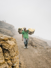 Man carrying sulfur extractions in mist